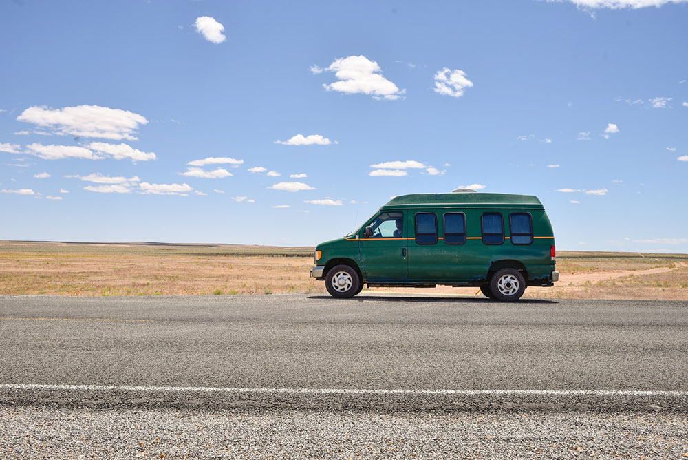 green van on road looking to make passive income living the van life