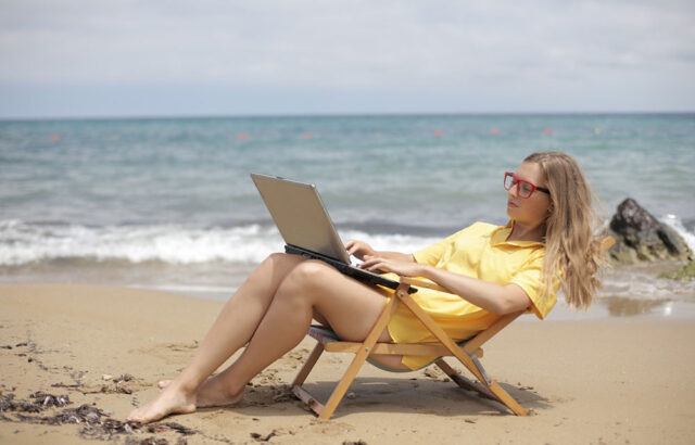 Girl on beach working on her laptop as a digital nomad
